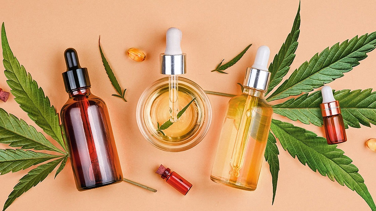 CBD oil bottles and droppers in medium and small size in a pink background lying on hemp leaves