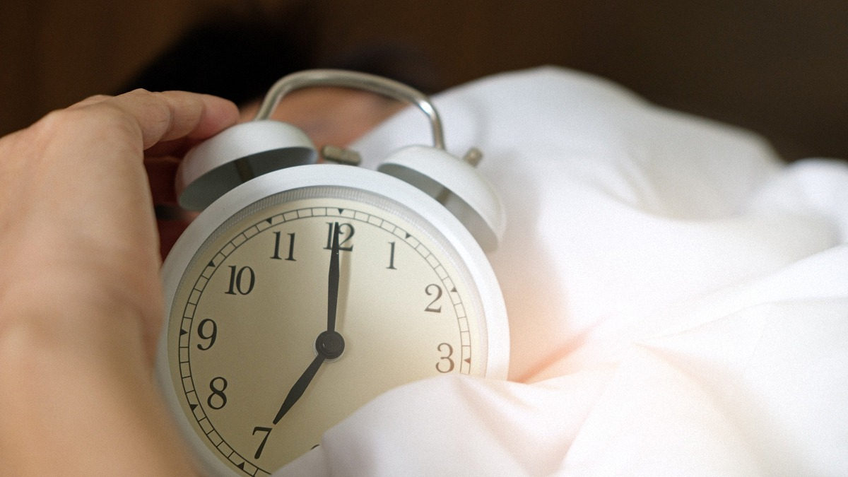 person holding an alarm clock in bed at seven in the morning