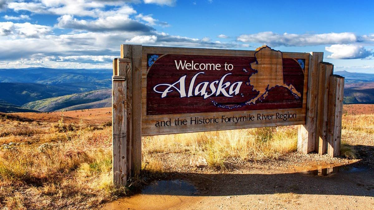 Welcome to Alaska sign by the mountain