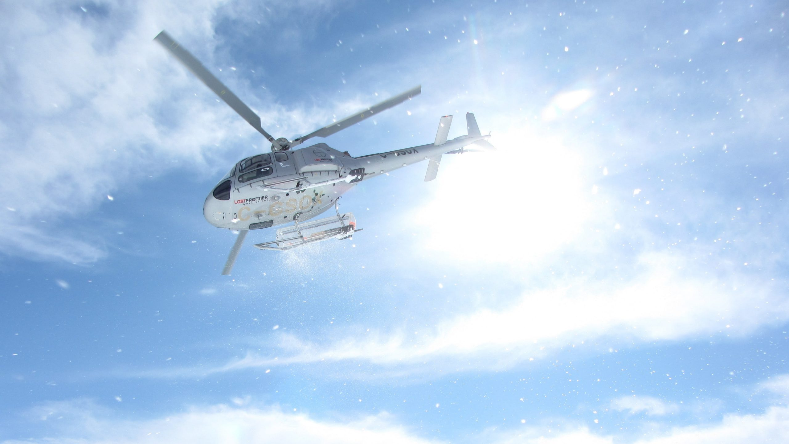 Photo of a helicopter flying in Alaska in blue sky background