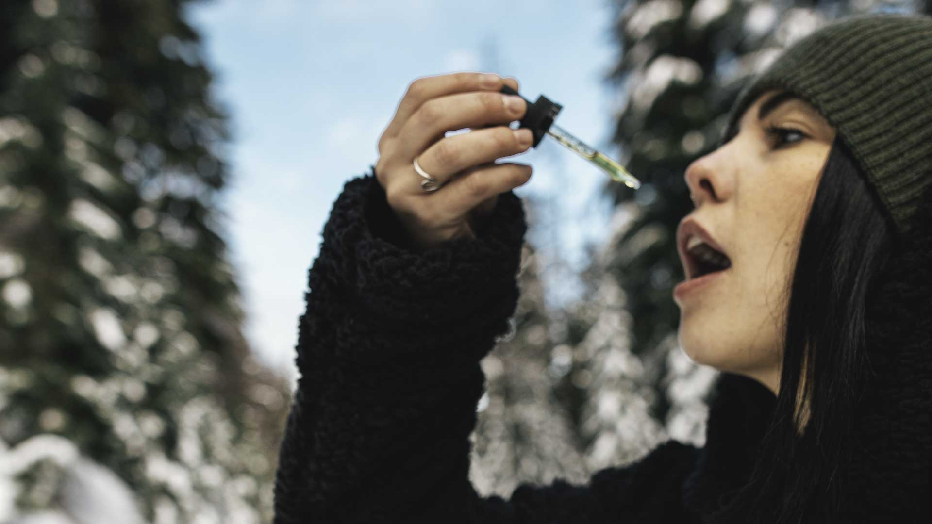 woman taking cbd from a dropper in a snow background