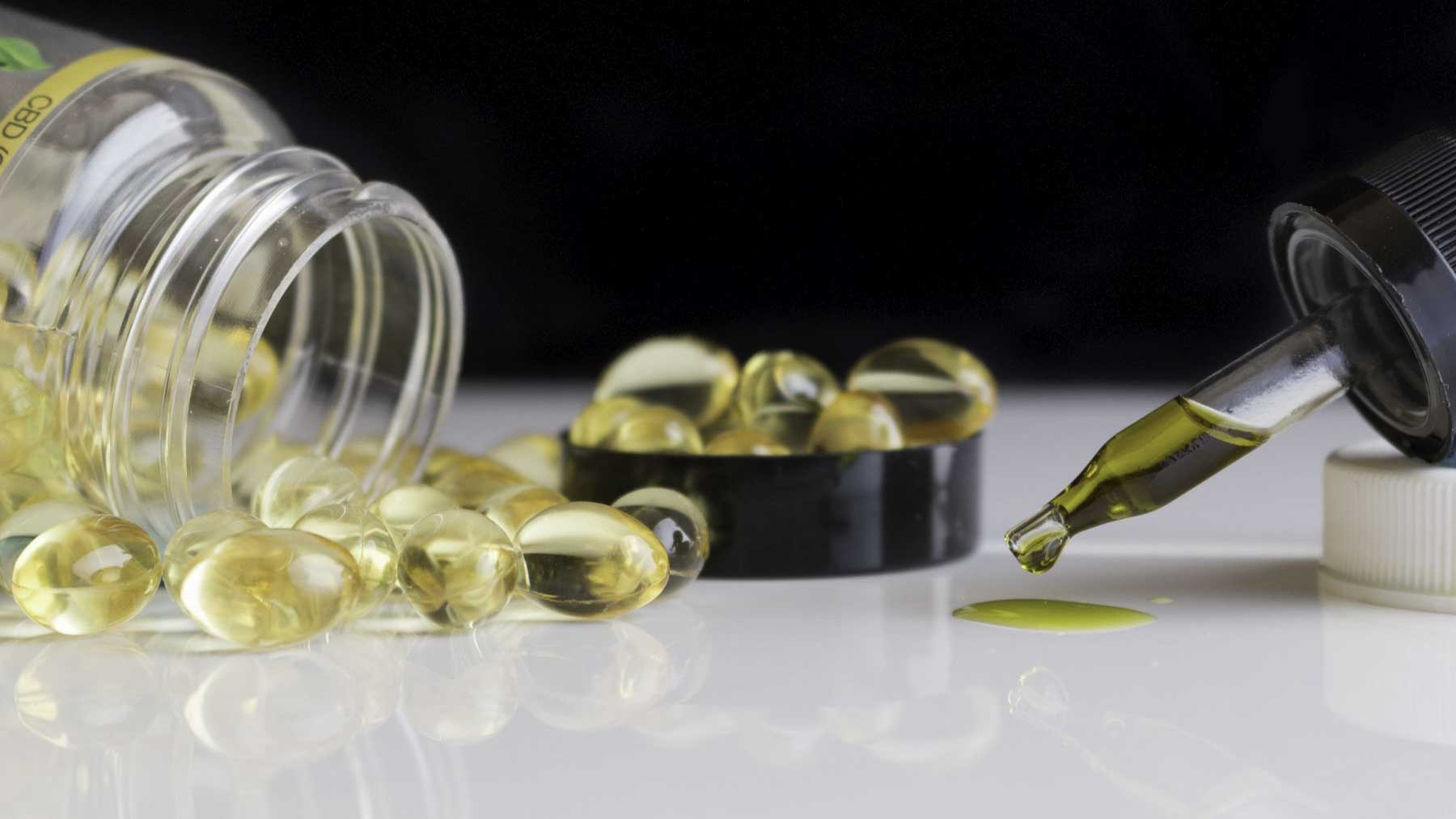 CBD capsules from a plastic bottle lying on a white surface