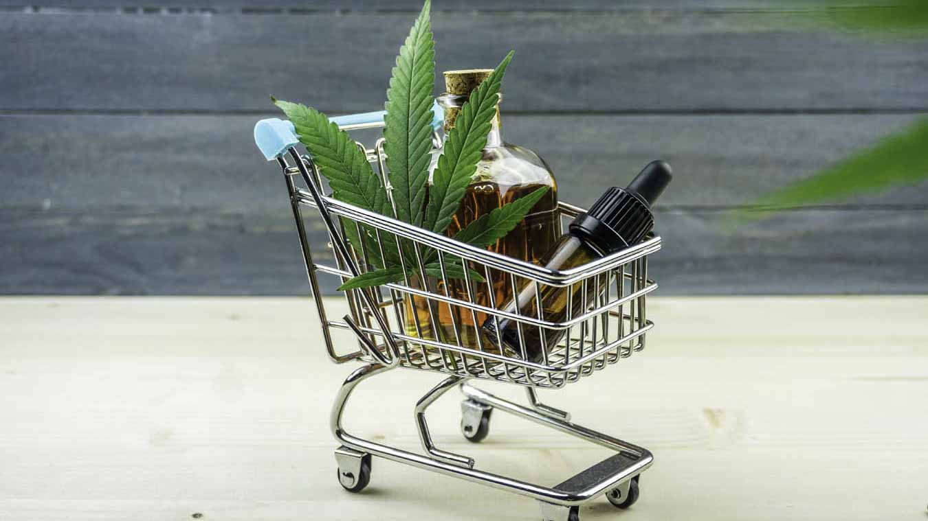 cbd oil products and a hemp leave on a tiny cart