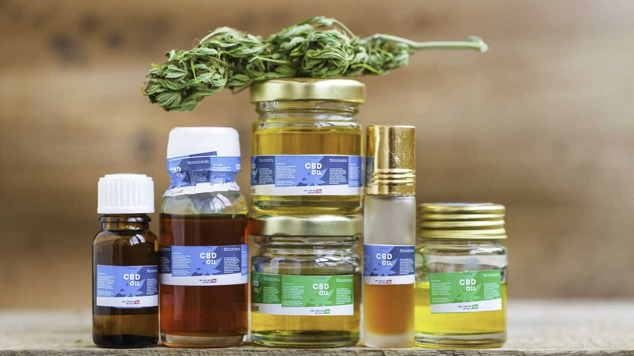 Image of CBD products and hemp bud on top of each other on a wooden table