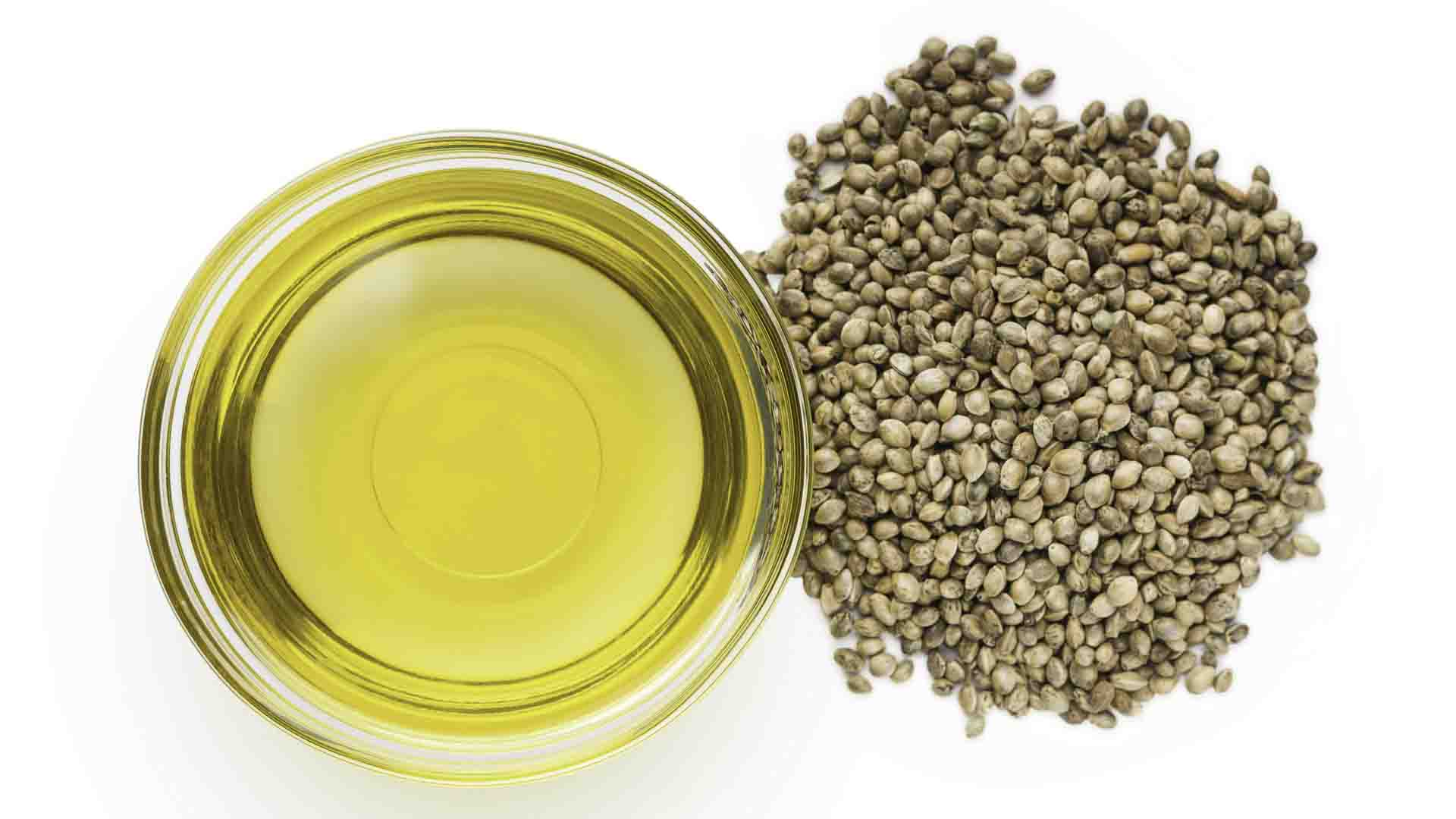Hemp oil inside a glass bowl with hemp seed on the side in pure white background