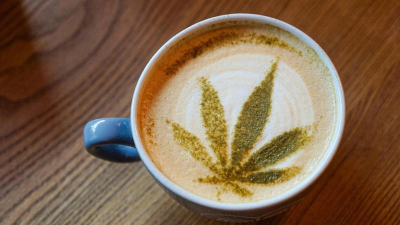 a cup of coffee with hemp leaf design on top