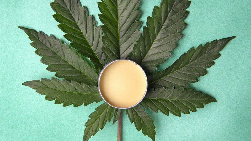 CBD Topical put in the center of a large hemp leaf in blue green background