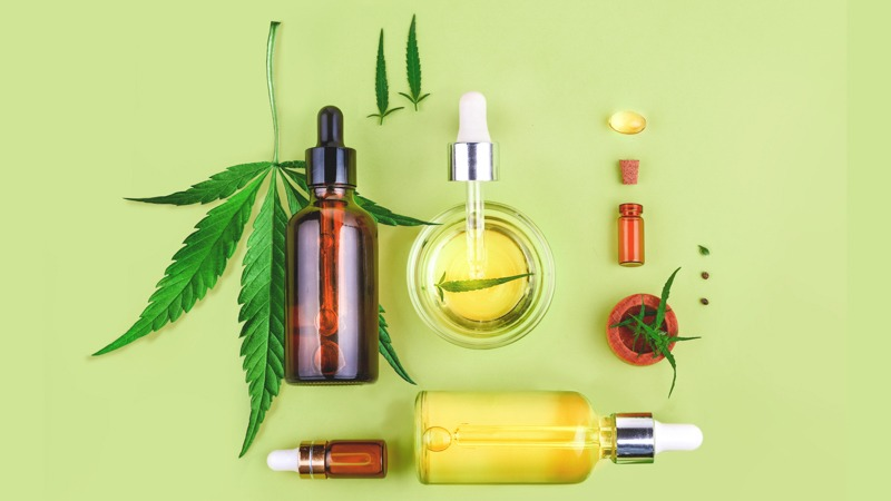CBD oil in bottles with hemp leaf in a yellow green background