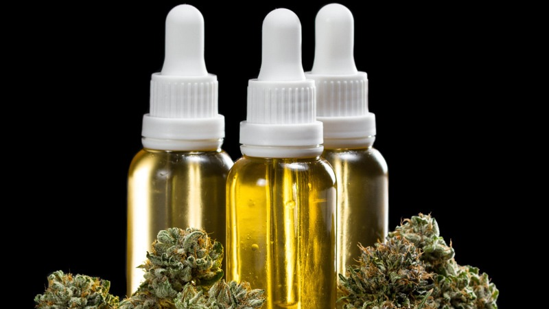 Three Bottles of CBD Oil with Hemp in a Black Background