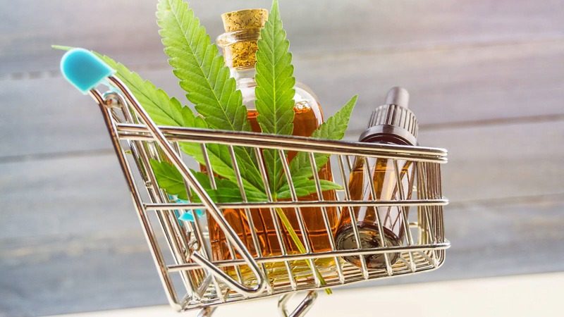 supermarket trolley with marijuana leaf and CBD oil