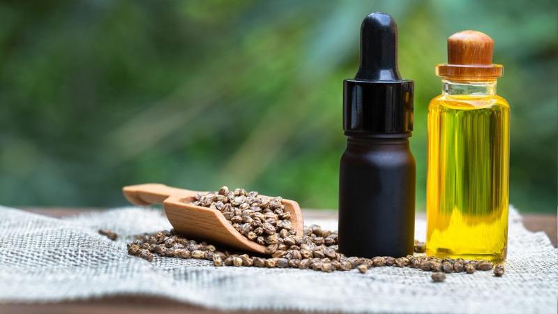 CBD Oil and Hemp Oil with Hemp Seeds On a Knit Surface