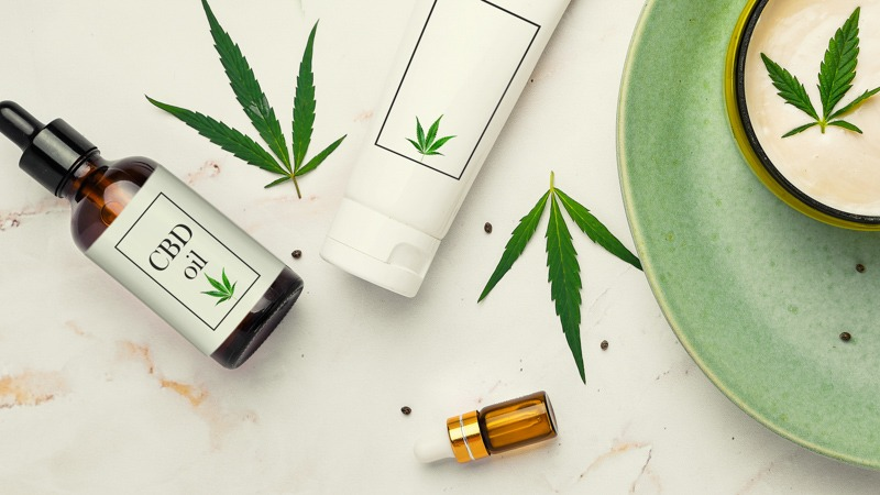 CBD Products with Hemp Leaves in a Turquoise Plate and Creamy Marble Surface