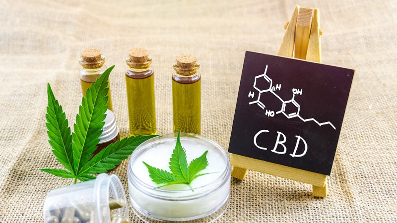 CBD Products with CBD Molecular Structure in a black board with stand