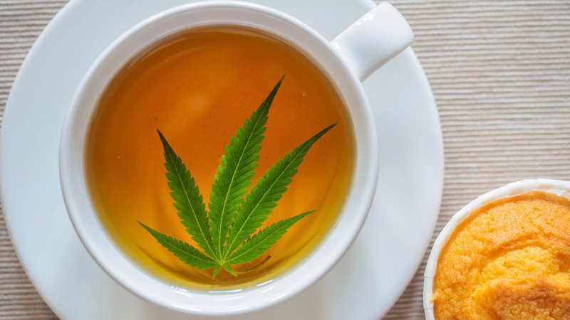 Hemp Leaf on Tea Placed in White Cup and Saucer Beside a Muffin