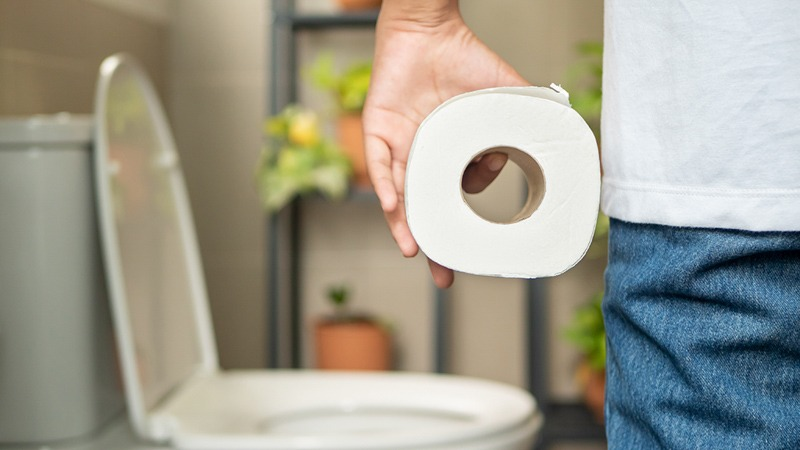 Person Holding a Tissue in a Toilet