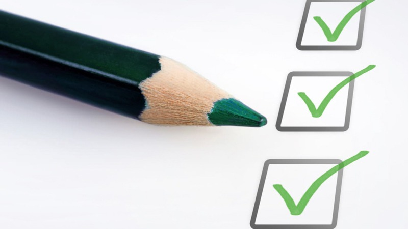 Checklist with Green Pencil on a White Paper