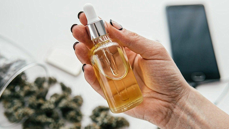 Hand holding a bottle of CBD oil extract with dried hemp flowers and a phone at the back