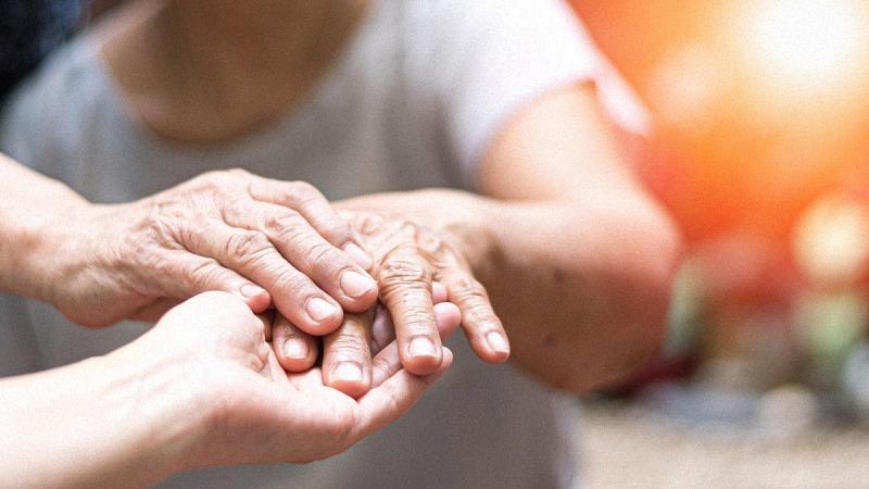 A doctor physician hand on an elderly senior with Parkinson's Disease