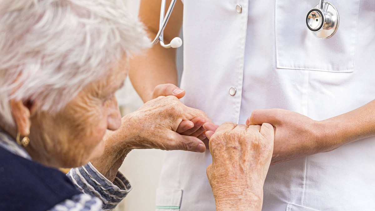 doctor holding an elderly woman diagnozed with Parkinson's Disease