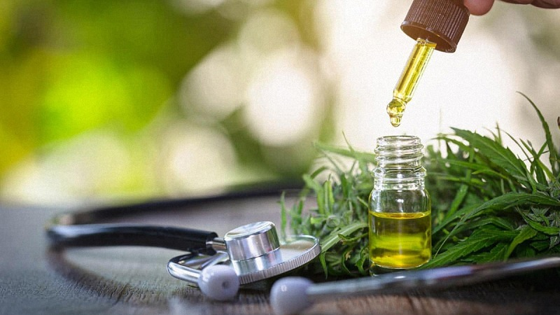 CBD oil dropper, cannabis leaves and a stethoscope on a wooden table