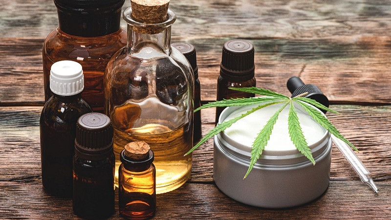 Cannabidiol extract in bottles a dropper and a topical cream with a hemp leaf on top