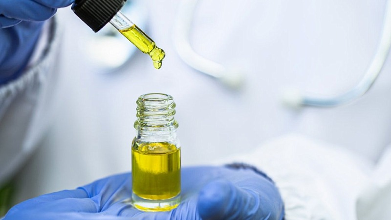Doctor taking CBD oil using a dropper